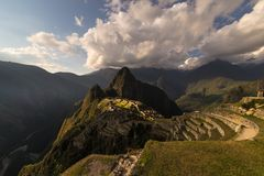 Machu Picchu belichtet durch das warme Sonnenunterganglicht Weitwinkelansicht von den Terrassen oben mit szenischem Himmel und So Stockfotos