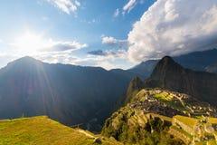 Machu Picchu belichtet durch das warme Sonnenunterganglicht Weitwinkelansicht von den Terrassen oben mit szenischem Himmel und So Stockfotografie