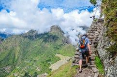 MACHU PICCHU, CUSCO, PERU 4 JUNI, 2013: Toerist die de berg van Huayna Picchu voor het beste panorama van Machu Picchu beklimmen stock afbeelding