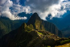 Machu Picchu illuminated by sunlight coming out from the opening clouds. The Inca`s city is the most visited travel destination i royalty free stock images