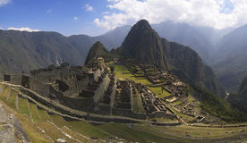 Machu Picchu panorama. Machu Picchu, main gate, surrounding wall and exterior stairway under uneven sunlight. Wayna Picchu and surrounding mountains in the Stock Image