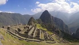 Machu Picchu panorama. Machu Picchu, main gate, surrounding wall and exterior stairway under uneven sunlight Royalty Free Stock Photo