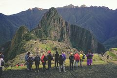 A group of tourists are looking at the Lost city of the Incas and taking photos in the foreground. Machu Picchu, Peru: August 14th, 2018: A group of tourists stock photo