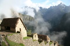 Machu Picchu - Restoration. Restored homes on the terraces of Machu Picchu. Each home has an authentically restored thatch roof. The terraces look down on the Royalty Free Stock Image