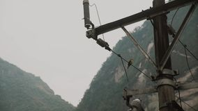 Bird on wire,mountains of Machu Picchu on the background.Tourists on Machu Picchu.