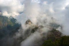 Machu Picchu som är upplyst vid det första solljuset som är kommande från öppningen, fördunklar ut Staden för Inca` s är den mest fotografering för bildbyråer