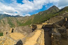 Machu Picchu som är upplyst vid det sista solljuset Den breda vinkelsikten över glöda terrasserar underifrån med scenisk himmel M fotografering för bildbyråer