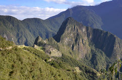 Machu Pichu with Huayna Picchu from far. View of Machu Pichu with Huayna Picchu from far, rainforest jungle and mountains with blue sky in the background royalty free stock images