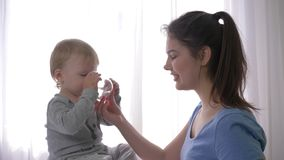 Macierzyńska opieka, szczęśliwa roześmiana berbeć chłopiec pije czystą wodę mineralną od szkła od uśmiechniętej matki wręcza i ra zdjęcie wideo