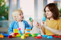 Macierzyści bawić się kolorowi budowa bloki z jej synem Zdjęcie Royalty Free