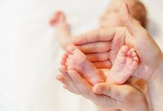 Macierzyści mienia dziecka cieki przy rękami Obrazy Stock
