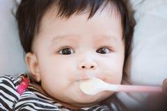 Macierzysta żywieniowa śliczna azjatykcia dziewczynka z łyżką w domu Zdjęcie Stock