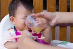 Macierzysta żywieniowa polewki woda dla dzieciaka osiem miesięcy w domu Zdjęcia Royalty Free