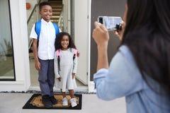 Macierzysta Bierze fotografia dzieci Z telefonem komórkowym Na Pierwszy dnia plecy Przy szkołą fotografia stock