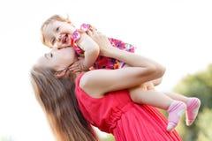 Macierzysta całowania dziecka córka w menchii sukni, obrazy royalty free