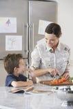 Macierzysta ciapanie marchewka Podczas gdy syna łasowanie Przy kuchnią fotografia royalty free