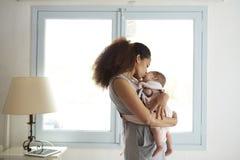 Macierzysta Cuddling dziecko córka Przed okno W Domu Obrazy Stock
