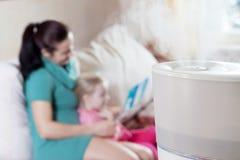 Macierzysta czytelnicza książka jej córka na tle humidif Zdjęcia Royalty Free