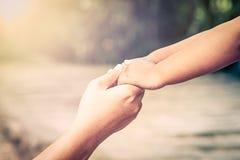 Macierzysta i dziecko jej mienia ręka wraz z miłością w parku Zdjęcia Stock