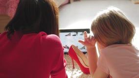 Macierzysta i mała córka patrzeje obuwie podczas gdy robiący zakupy online na cyfrowej pastylce Pojęcie online zakupy zbiory