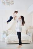Macierzysta i mała córka bawić się w sypialni Obrazy Stock