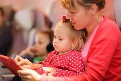 Macierzysta i mała córka patrzeje dotyka ochraniacza wewnątrz zdjęcia royalty free