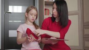 Macierzysta i mała córka patrzeje obuwie podczas gdy robiący zakupy online na cyfrowej pastylce Pojęcie online zakupy zdjęcie wideo