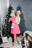 Macierzysta i mała córka pozuje w nowego roku wnętrzu Zdjęcie Royalty Free