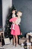 Macierzysta i mała córka pozuje w nowego roku wnętrzu Zdjęcia Royalty Free