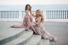 Macierzysta i mała córka w różowych balowych togach outdoors w lecie blisko pałac zdjęcia royalty free