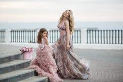 Macierzysta i mała córka w różowych balowych togach outdoors w lecie blisko pałac obraz royalty free