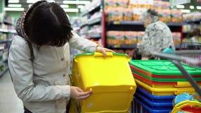 Macierzysta i mała córka wybiera plastikowego zbiornika dla zabawek w supermarkecie zbiory