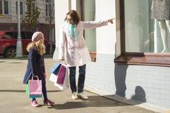 Macierzysta i mała córka z torba na zakupy Plenerowy, tła miasto, sklepów okno obraz royalty free