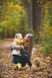 Macierzysta i mała córki blondynka zabawy odprowadzenie w jesień parku, kolorów żółtych życia wokoło Zdjęcie Royalty Free