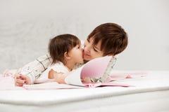 Macierzysta i mała dziewczynka czyta książkę na łóżku Zdjęcia Royalty Free