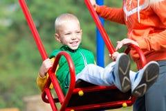 Macierzysta jazda jej mały syn na huśtawce Szczęśliwy weekend fotografia stock