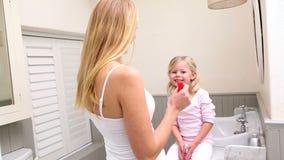 Macierzysta kładzenie wargi glosa na małej córce zdjęcie wideo
