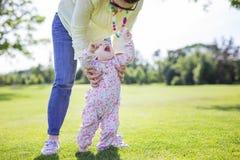Macierzysta podporowa dziecko córka i pomagać ona robimy pierwszym krokom na zielonej trawie w lato parku zdjęcia royalty free