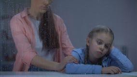 Macierzysta podporowa mała dziewczynka za dżdżystym okno, dzieciaka cierpienie od znęcać się zdjęcie wideo