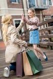 Macierzysta pozycja na jeden kolanie z torba na zakupy i dawać jego mała córka wysokość pięć fotografia stock