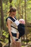 Macierzysta przewożenie córka w temblaku w lesie Obrazy Royalty Free