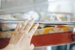 macierzysta ręka dosięga baby& x27; s łóżko zdjęcie stock