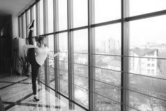 Macierzysta robi super wysoka nogi rozciągliwość w gym Zdjęcie Stock