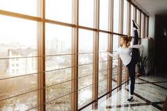 Macierzysta robi super wysoka nogi rozciągliwość w gym Obraz Royalty Free