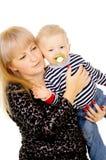 Macierzystego utrzymania wesoło mały dziecko w jej rękach, ssa pacyfikator zdjęcia stock