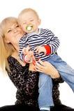 Macierzystego utrzymania wesoło mały dziecko w jej rękach, ssa pacyfikator obraz royalty free