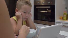 Macierzysty żywieniowy dziecko podczas gdy on dopatrywanie pastylki pecet zdjęcie wideo