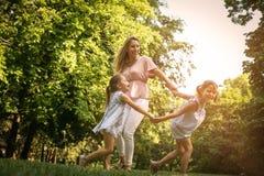 Macierzysty bawić się na łące z jej dwa małą córką fotografia royalty free