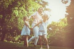 Macierzysty bawić się na łące z jej dwa małą córką obrazy royalty free