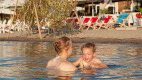 Macierzysty bawić się z jej młodym synem w plaży zbiory